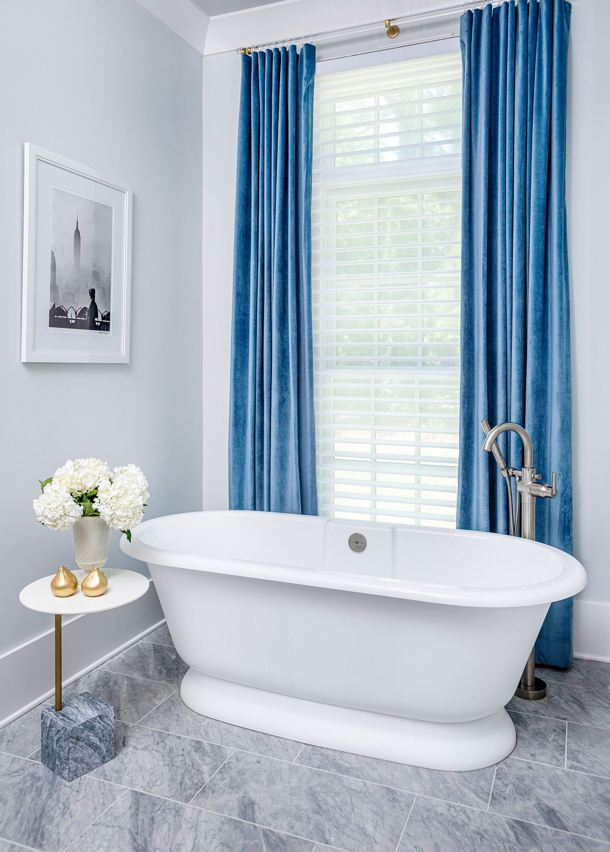 Drapes in blue add color to this bathroom in white with a modern minimal look