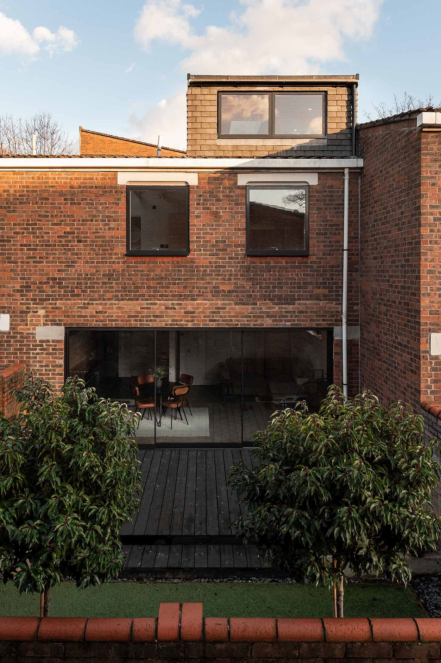 Facade of the London home in brick with glass walls and windows that offer textural contrast