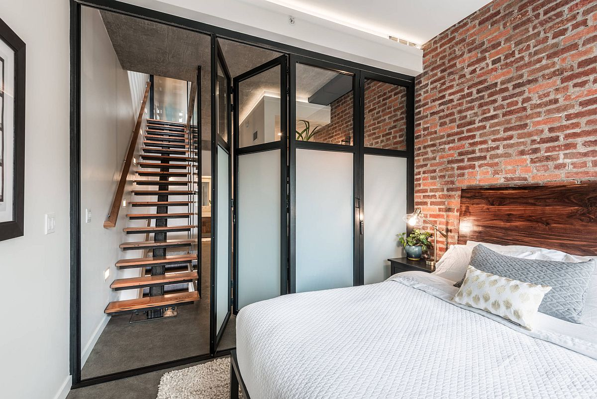 Folding-doors-and-a-neutral-backdrop-add-to-the-spacious-design-of-this-small-industrial-bedroom-with-accent-brick-wall-16720