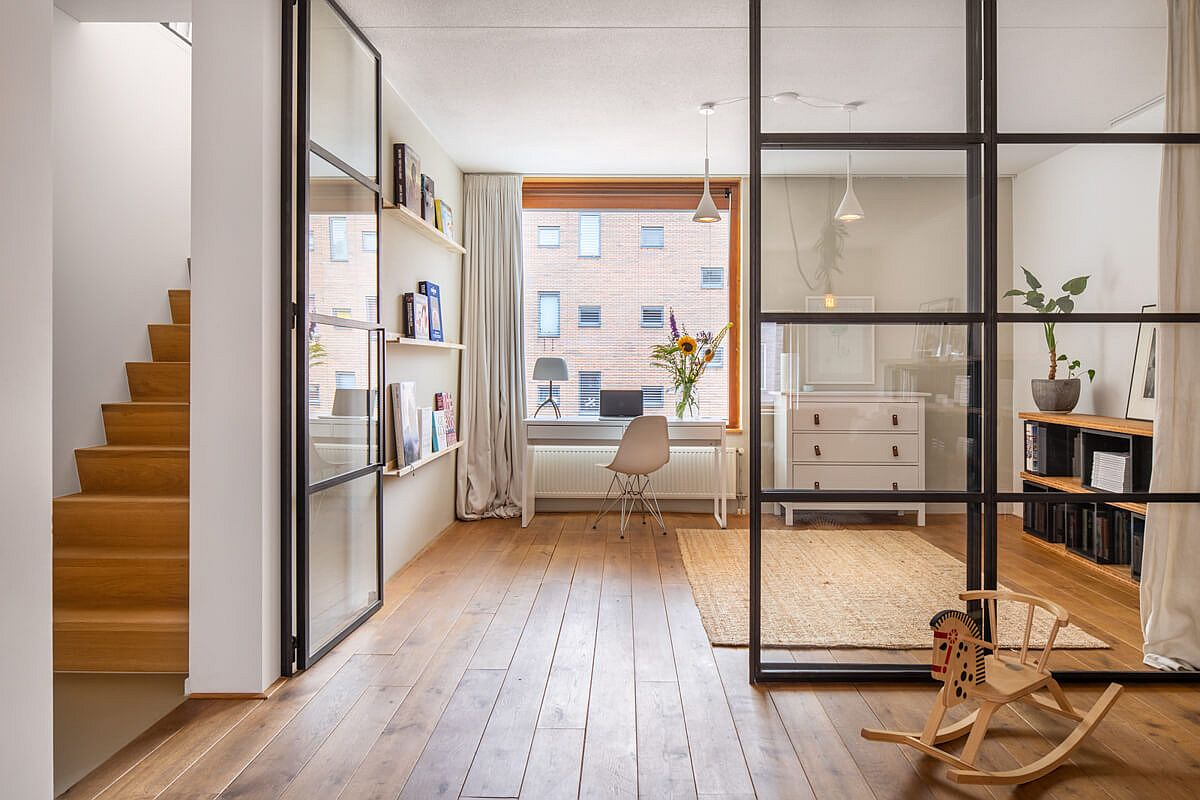 Framed glass wall delineate space without actually stoping the flow of light inside the Amsterdam home