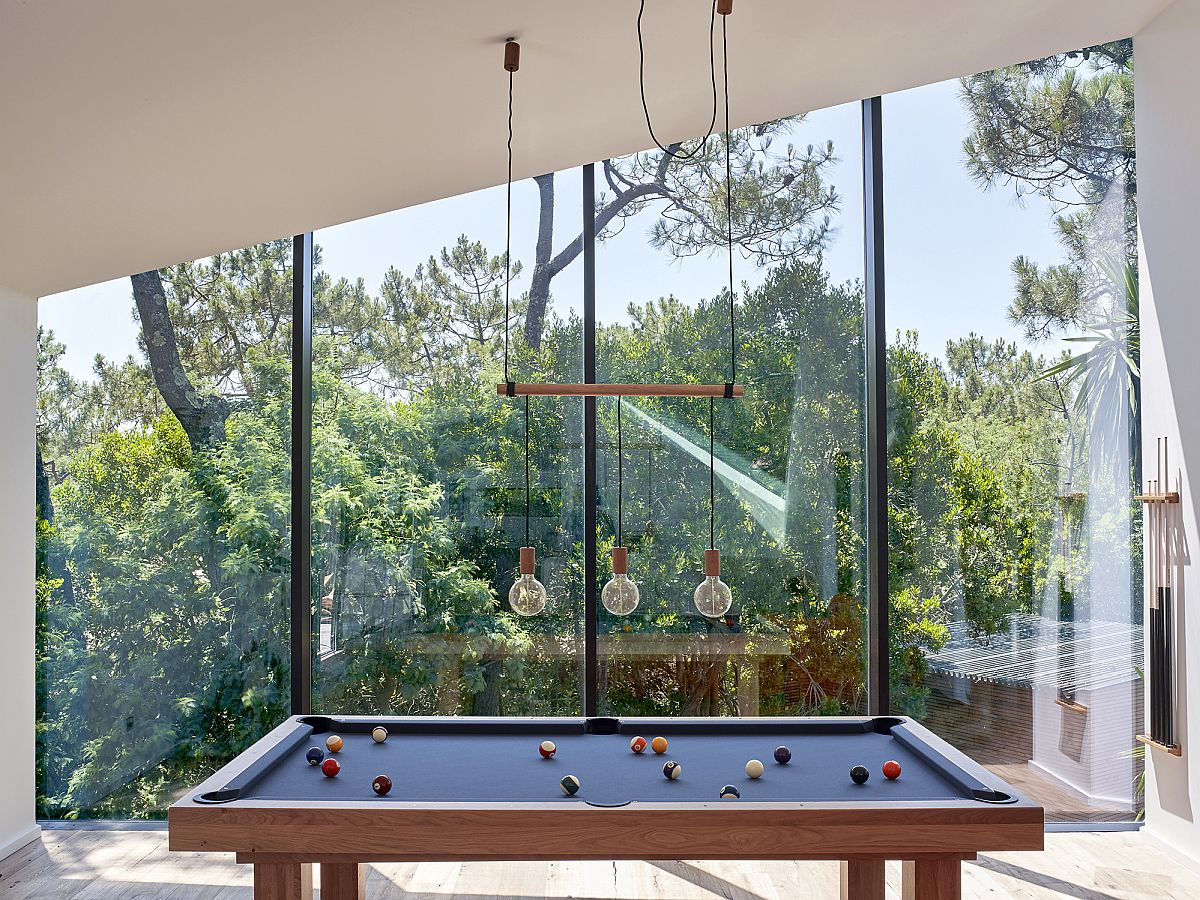 Game room on the upper level with glass walls offers lovely views of the landscape outside