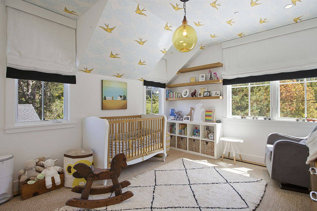 Gender-neutral modern farmhouse nursery in white with wallpaper on walls