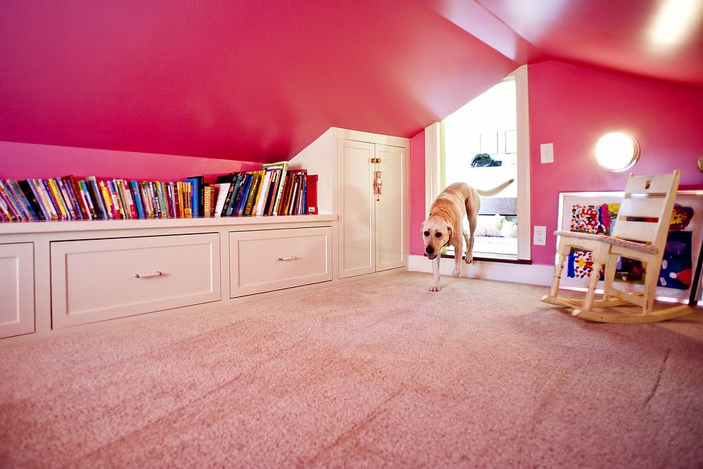 Girls' attic playroom with plenty of built-in shelving and walls draped in pink