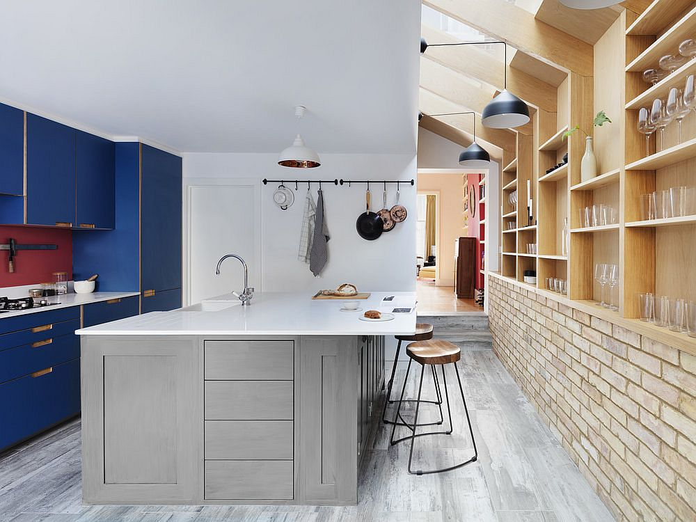 Gorgeous blue cabinets add color and contrast to the neutral kitchen with brick walls and wooden shelves