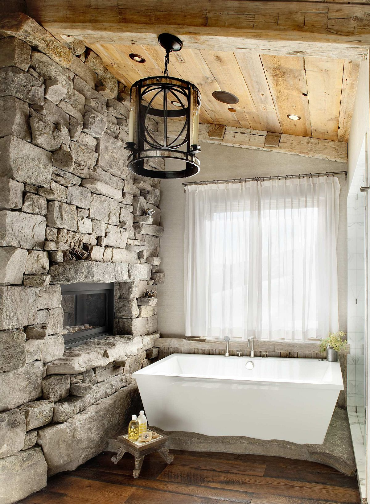 Gorgeous rustic bathroom with a stone wall, fireplace and a lovely tub in white