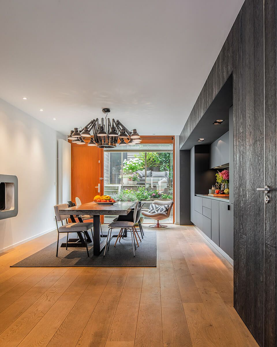 Gray single-wall kitchen along with dining area on the lower level of the house
