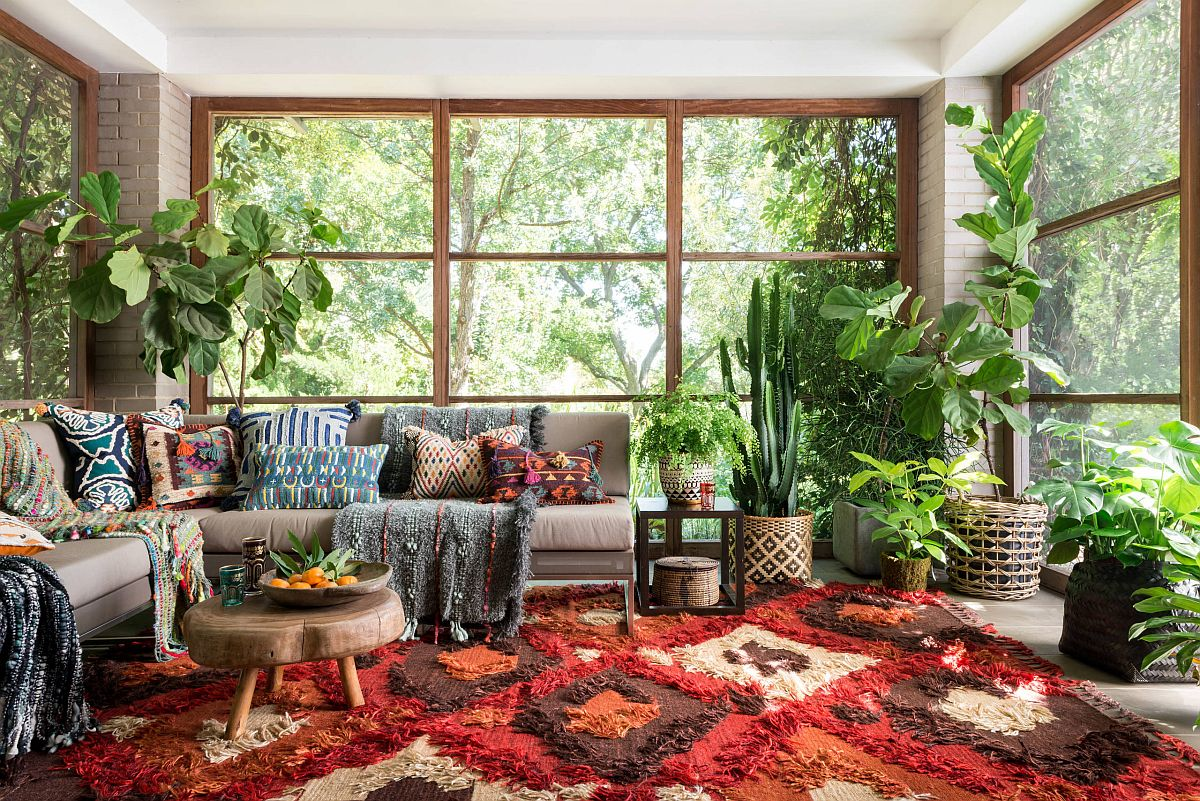 Greenery along with bright rug brings uniqueness to this eclectic sunroom full of vivacious charm