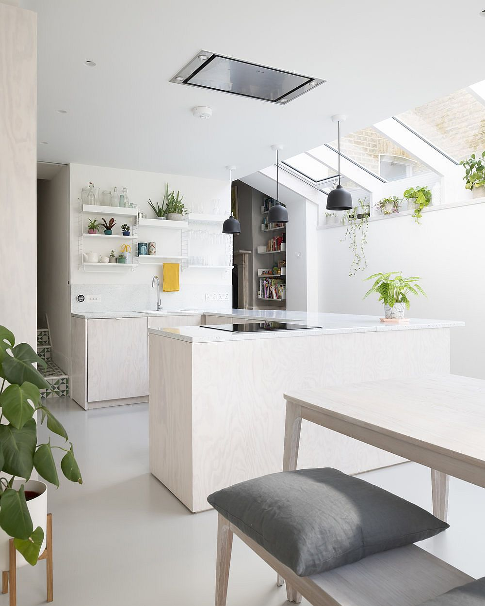 Greenery and accents in the kitchen bring color to an otherwise neutral interior in white