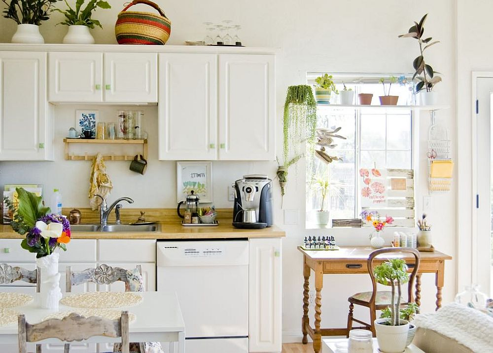 Indoor plants bring green tinge to this contemporary kitchen in white with a relaxed style