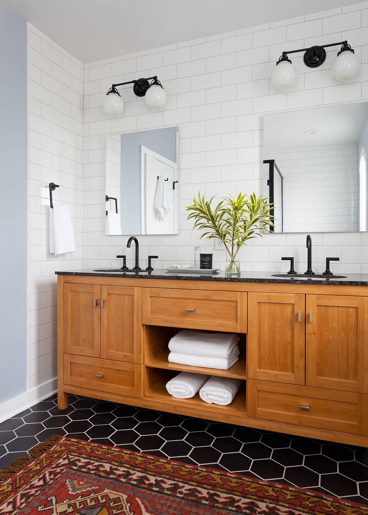 It is the floor that brings black to this black and white bathroom with a lovely wooden vanity