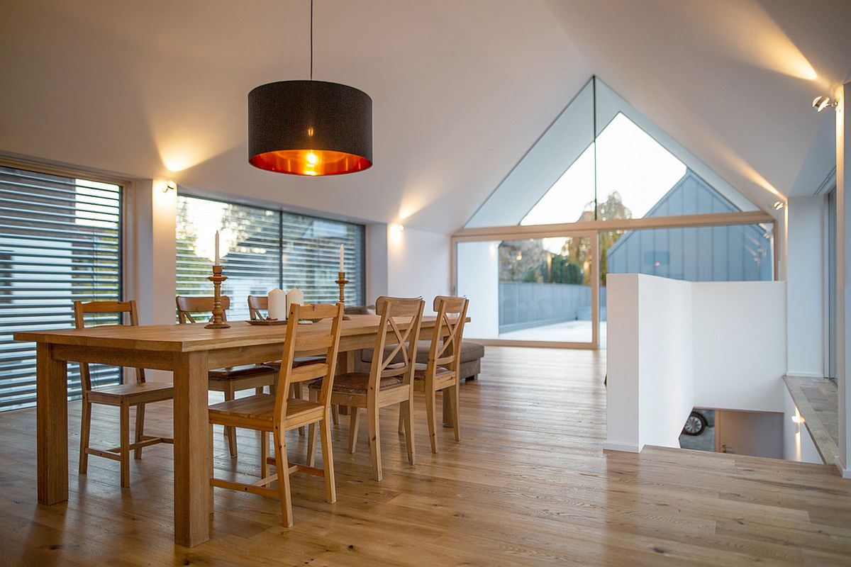 Large, oversized pendant in black illuminates the space above the dining table