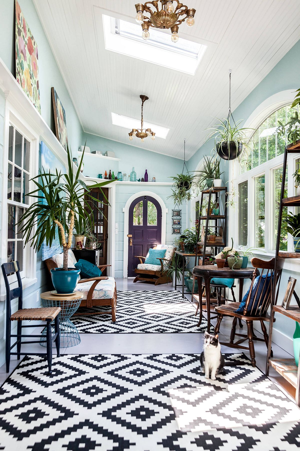 Light blue, white and black and white rugs combined to create a fabulous sunroom with eclectic flair