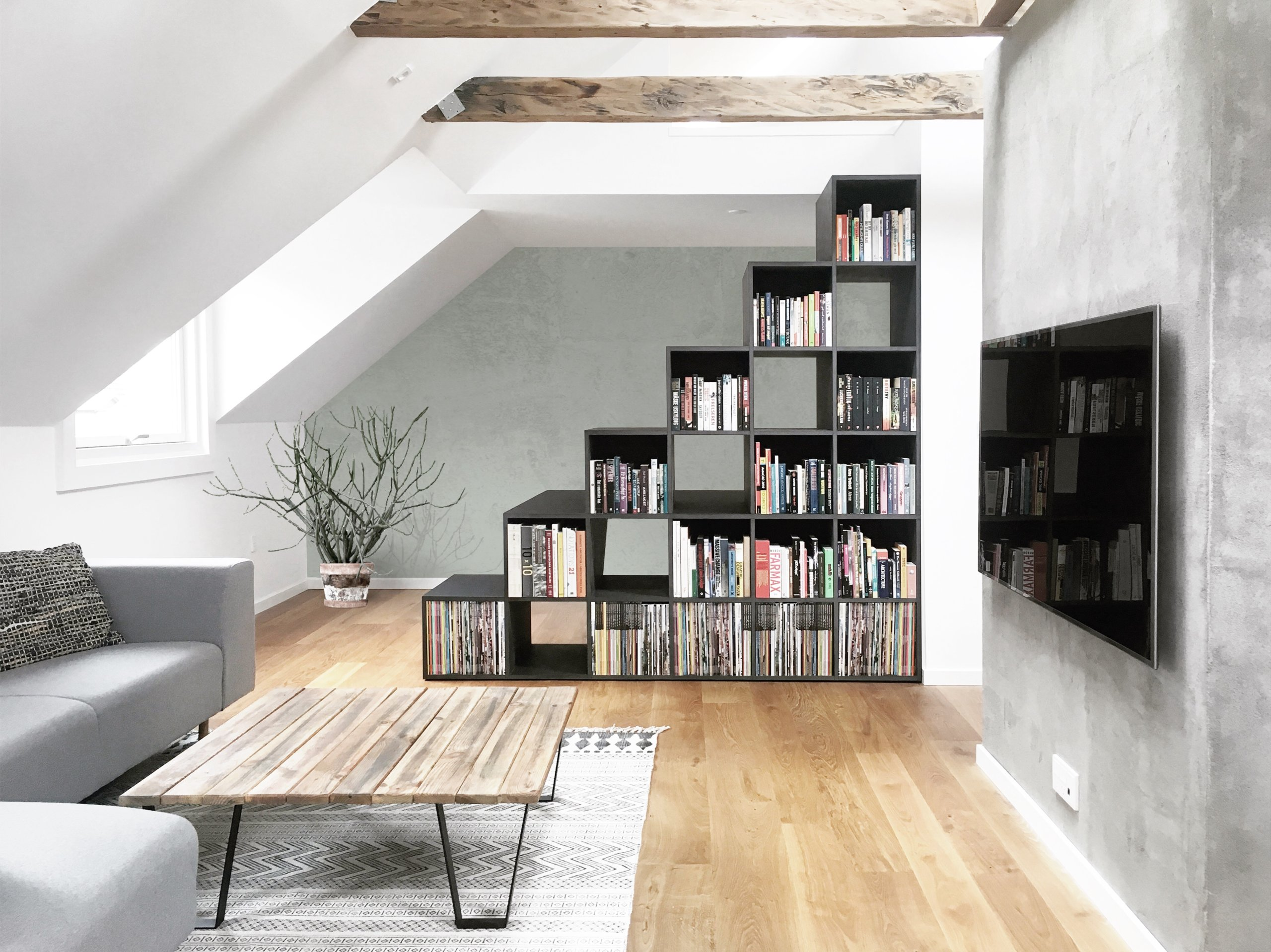 Living area in neutral hues with light gray couch and a lovely bookshelf