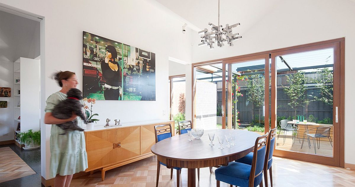 Lovely dining room with wooden credenza, round dining table and blue chairs