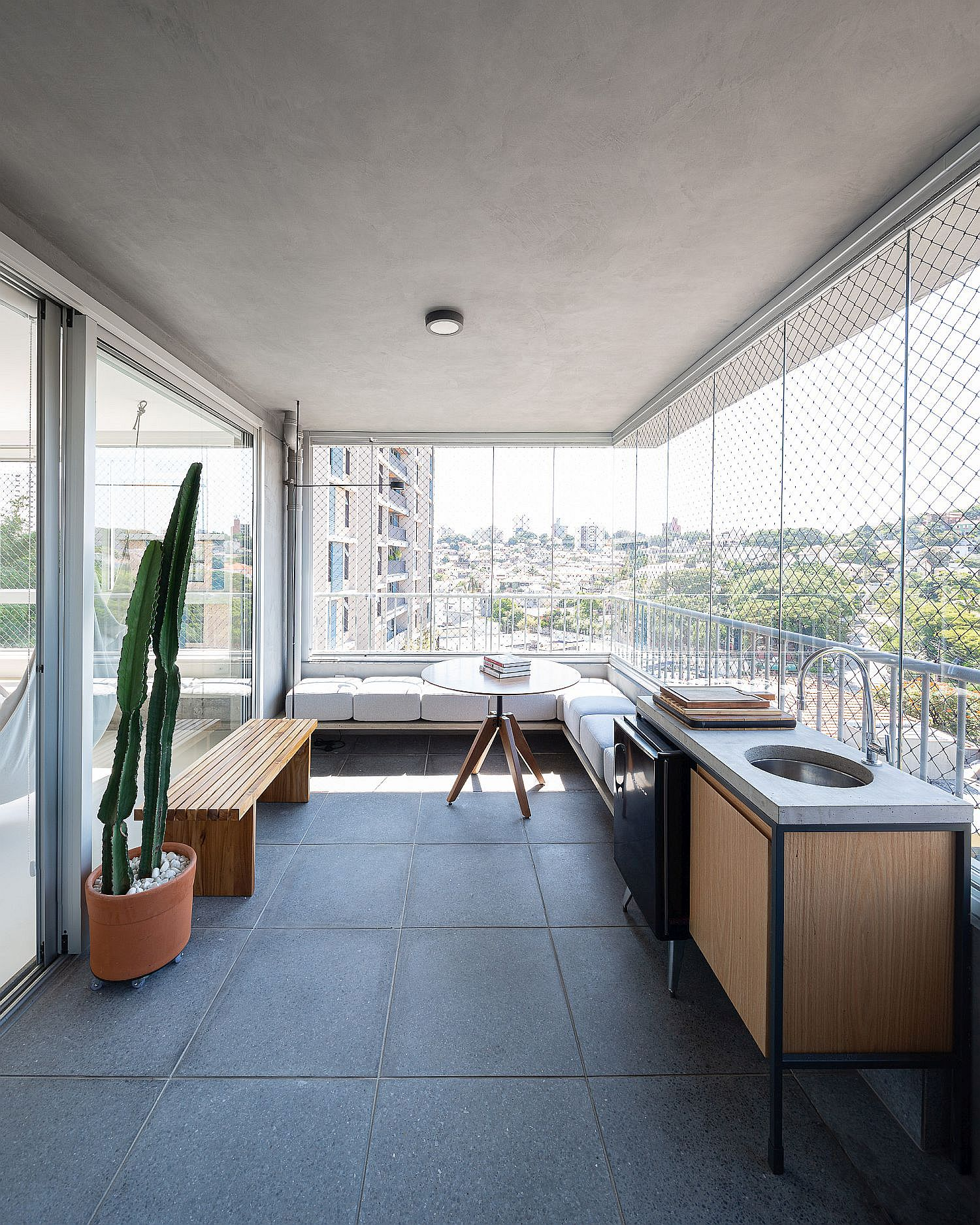 Mesh and glass walls for the balcony create a sheltered space that feels like an extension of the living room
