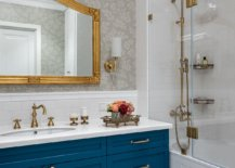 Modern-bathroom-in-white-with-blue-vanity-and-a-mirror-that-features-golden-frame-92755-217x155