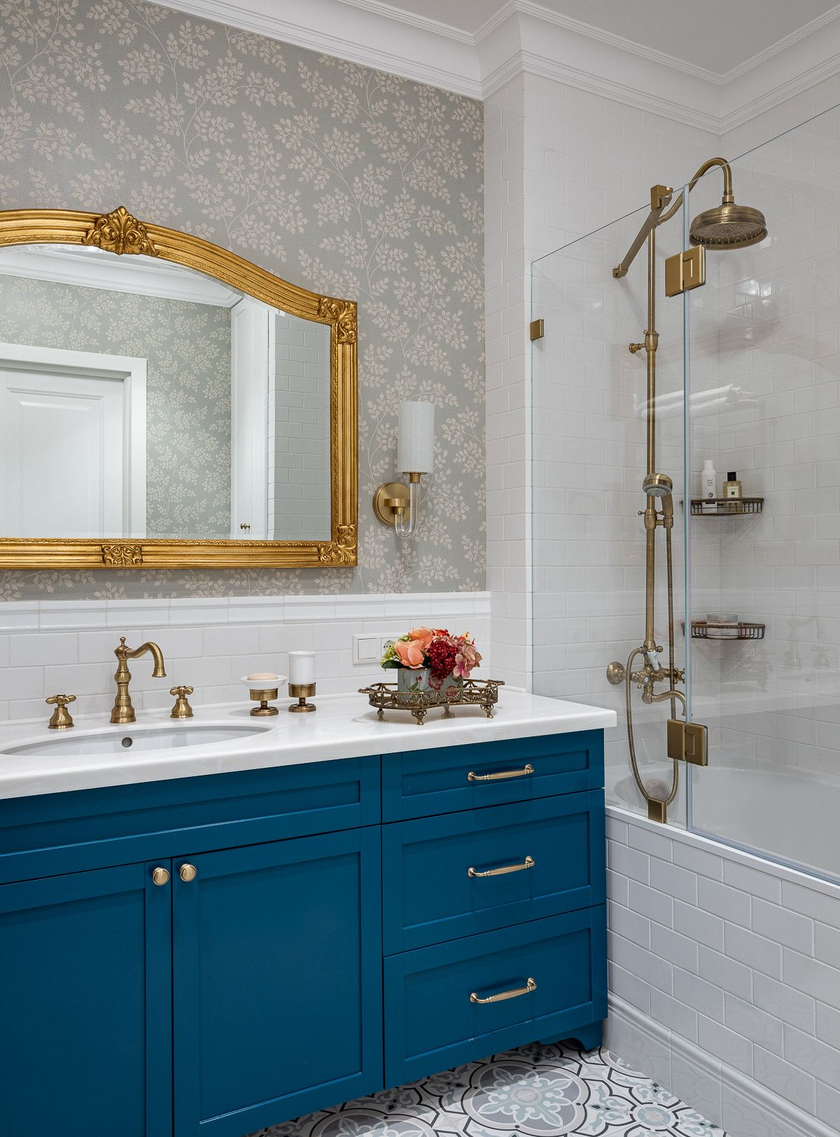 Modern bathroom in white with blue vanity and a mirror that features golden frame