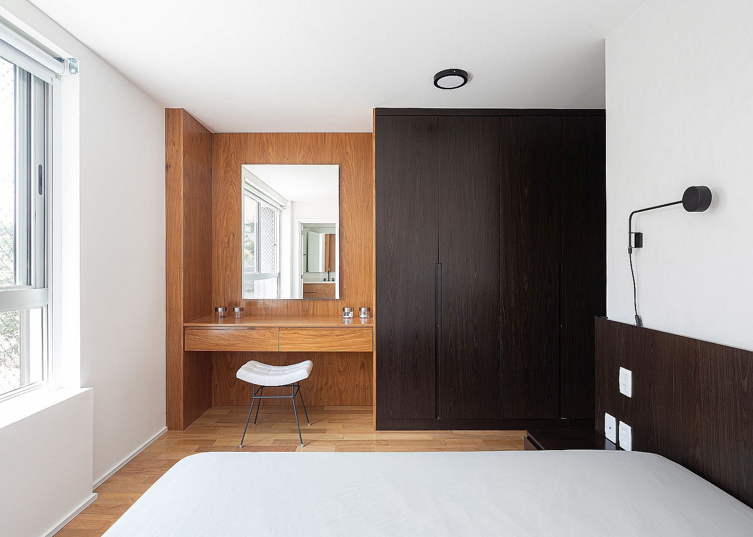 Modern bedroom of the apartment in white and wood feels elegant and understated