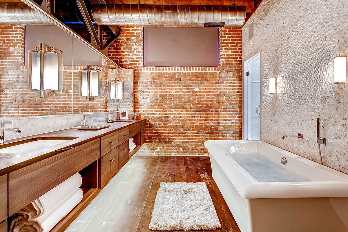 Modern industrial bathroom wih brick wall and wooden vanity along with bathtub in white