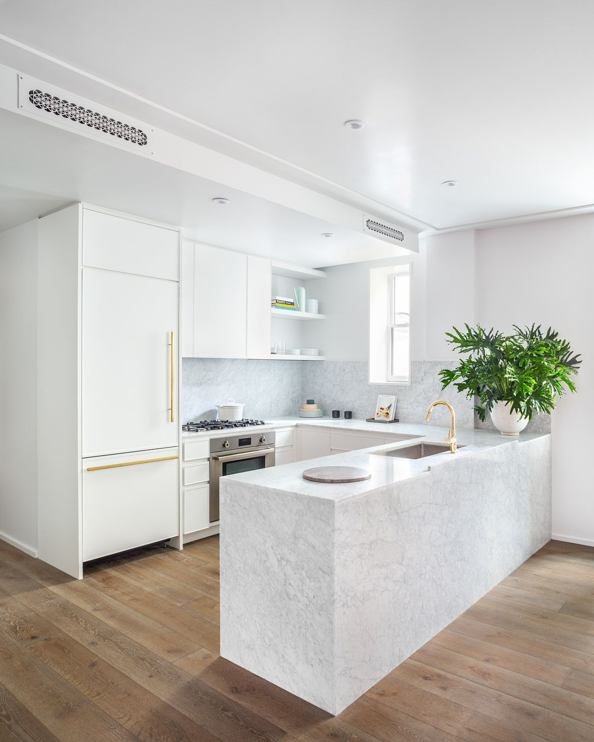 Monochromatic kitchen in white is filled with luxurious finsihes and marble surfaces