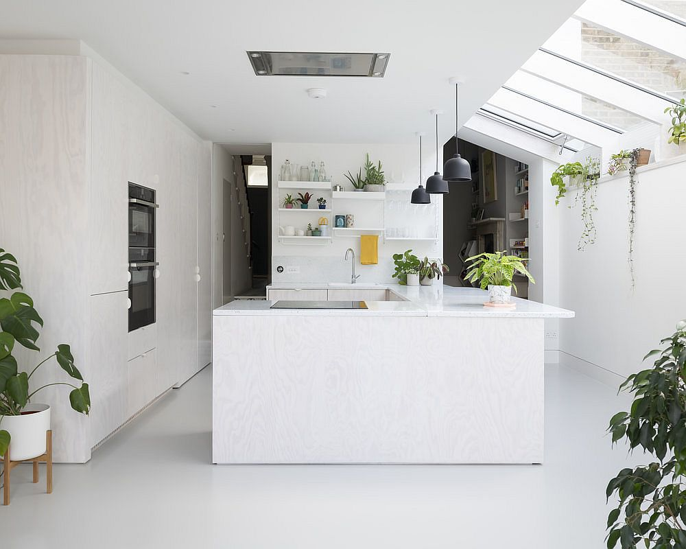 New kitchen and dining area of the British home in white acts as an interface between the old and the new