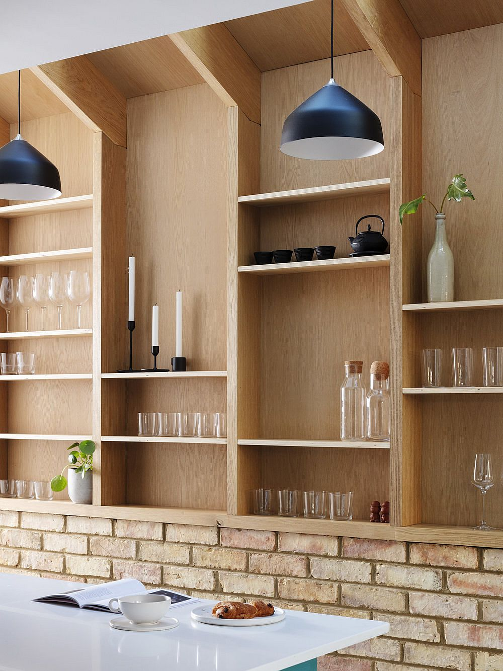 Pendants-in-black-add-visual-contrast-to-the-interior-draped-in-wood-and-brick-83569