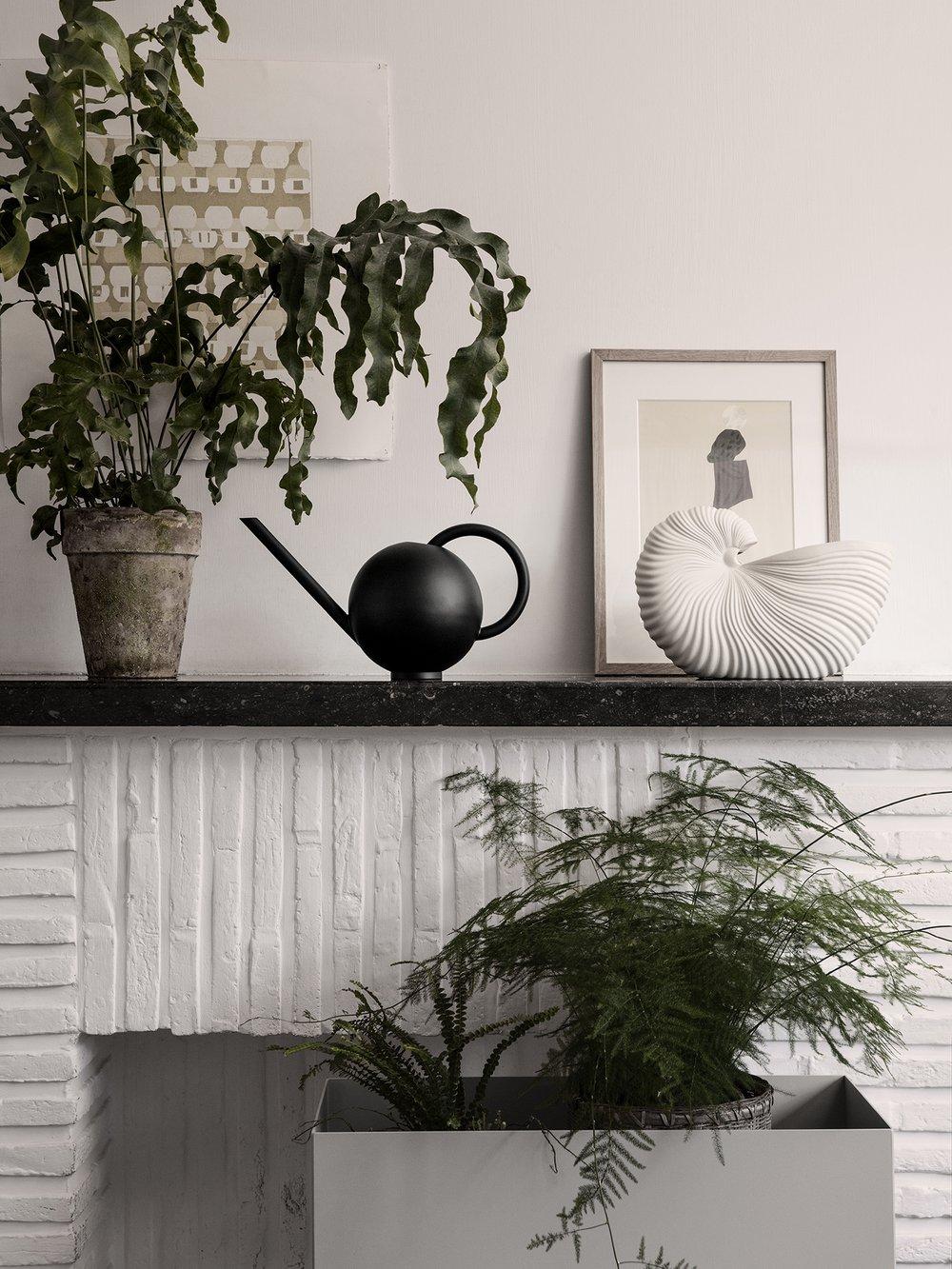 Plants adorn a vignette featuring decor from ferm LIVING