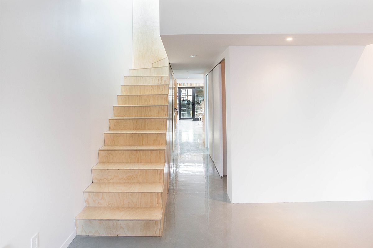 Plywood furniture and staircase inside the white revamped Artist's apartment in France