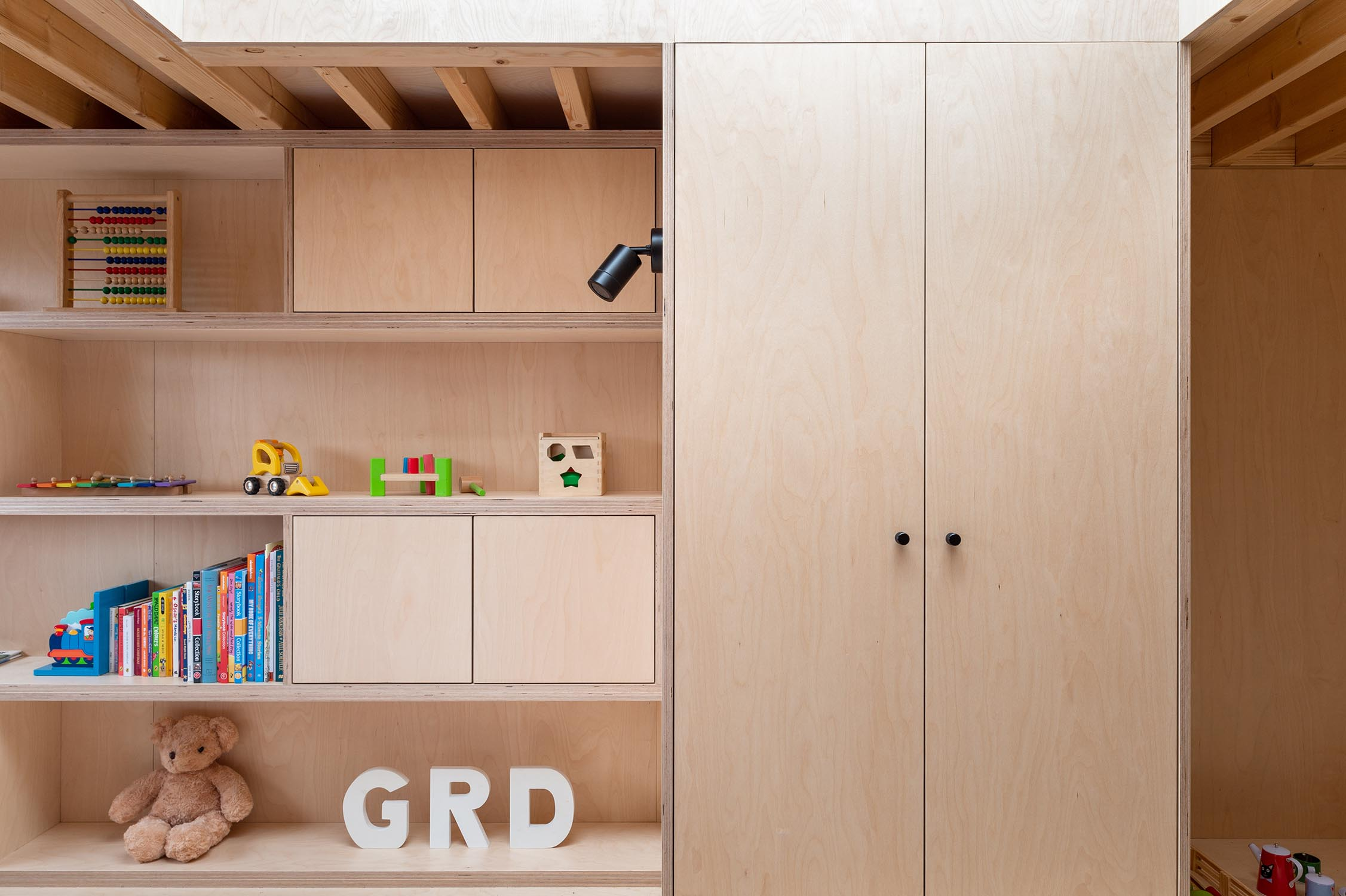 Plywood walls and cabinets along with shelves recreate the interior of this family home in London