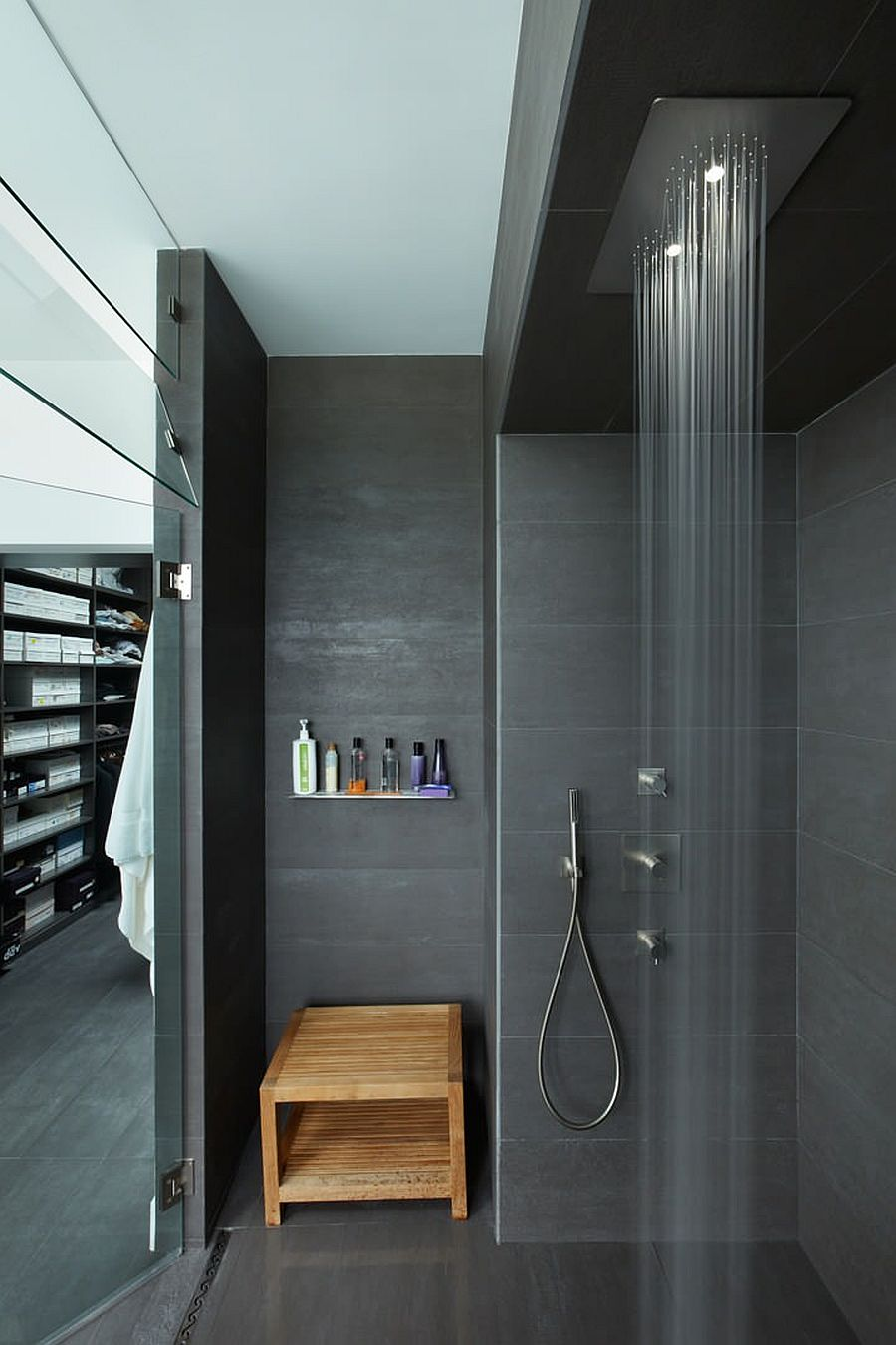 Polished bathroom in charcoal gray with rainfall shower and lovely lighting