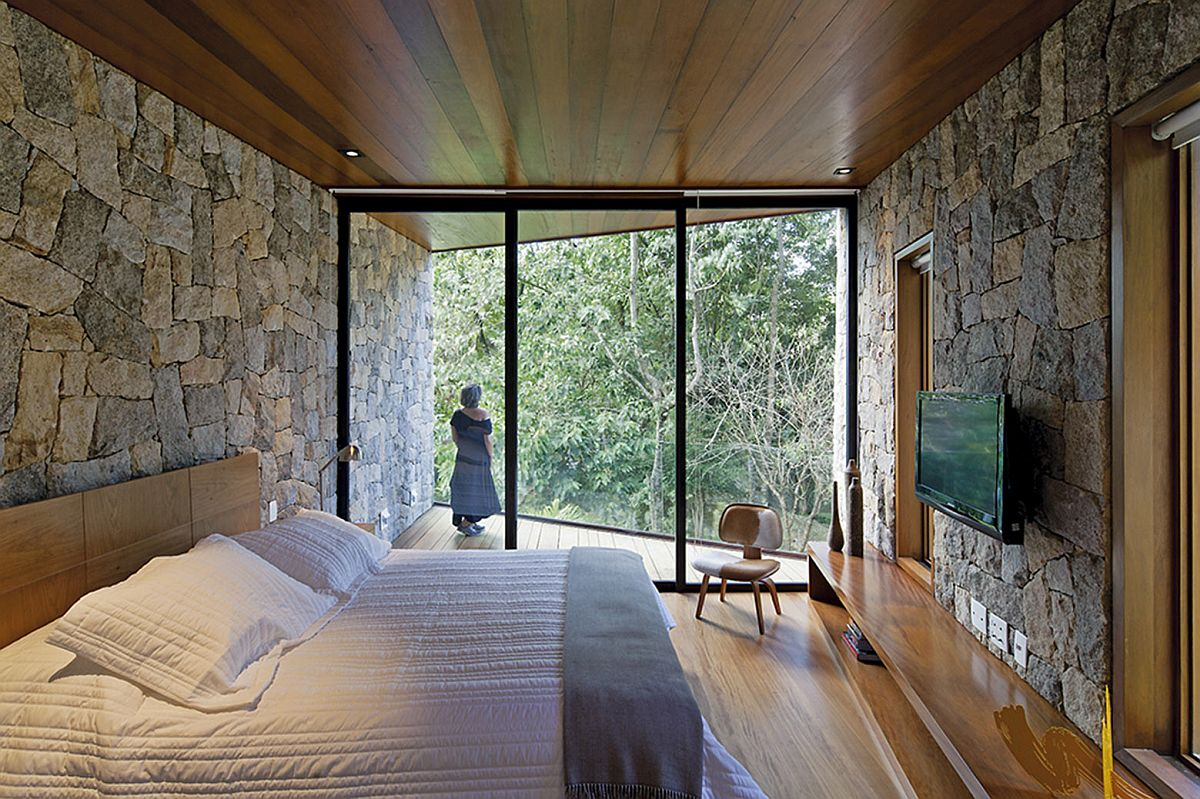 Relaxing retreat bedroom in wood and stone offers unabated views of the landscape