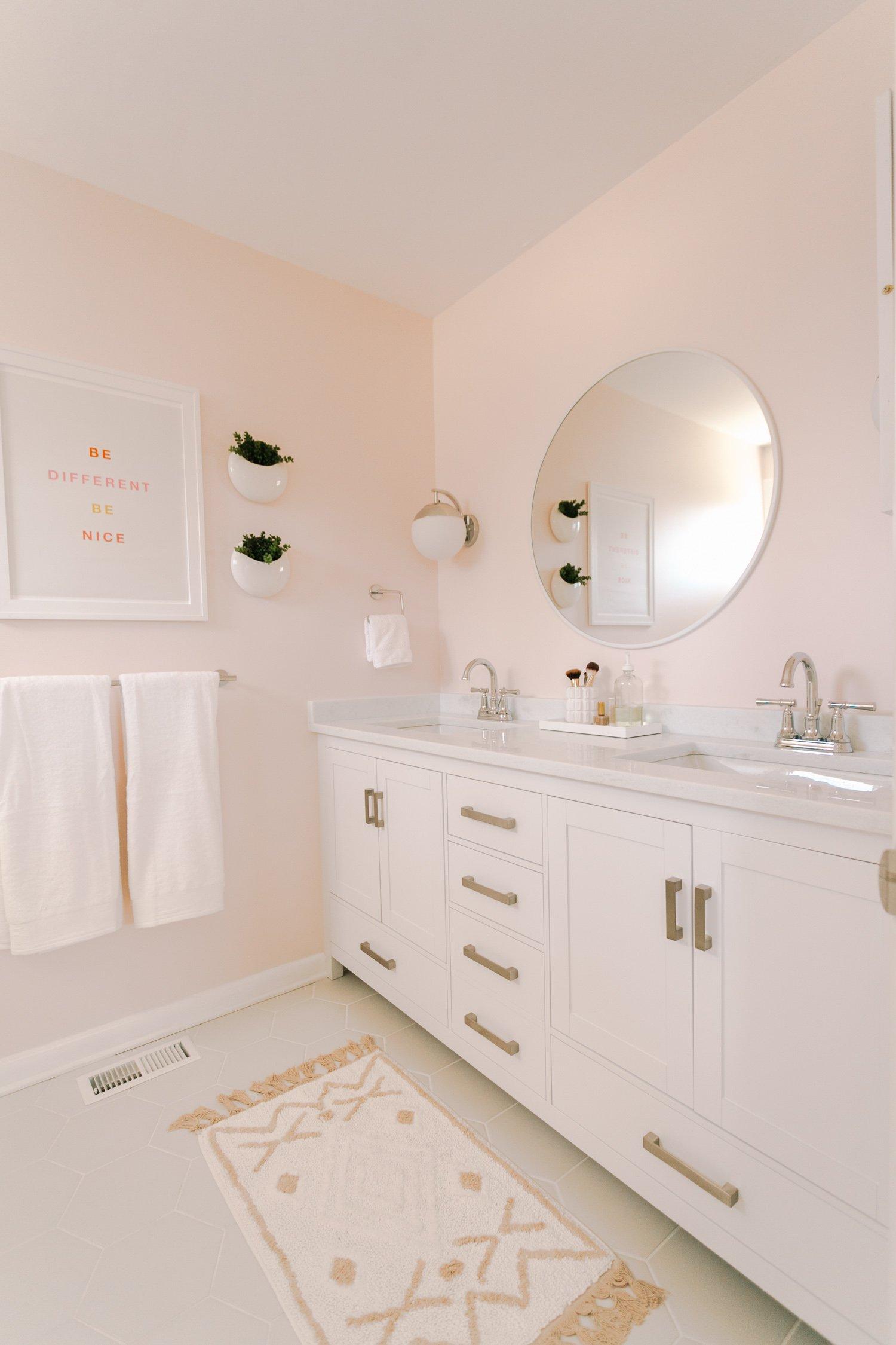 Round white mirror in a blush bathroom
