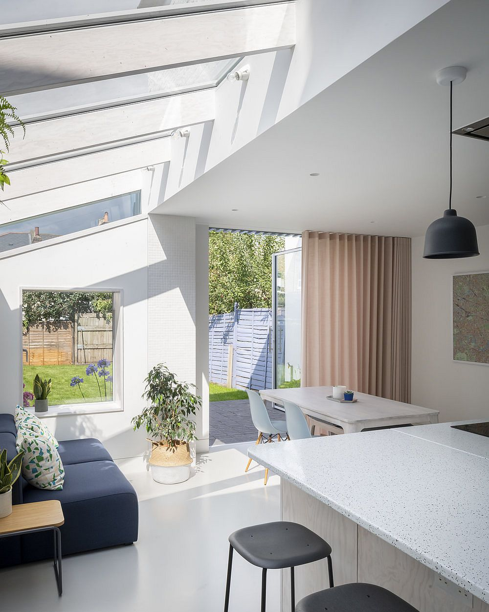 Seamless white resin floor and white walls create a spotless contemporary interior with ample natural light