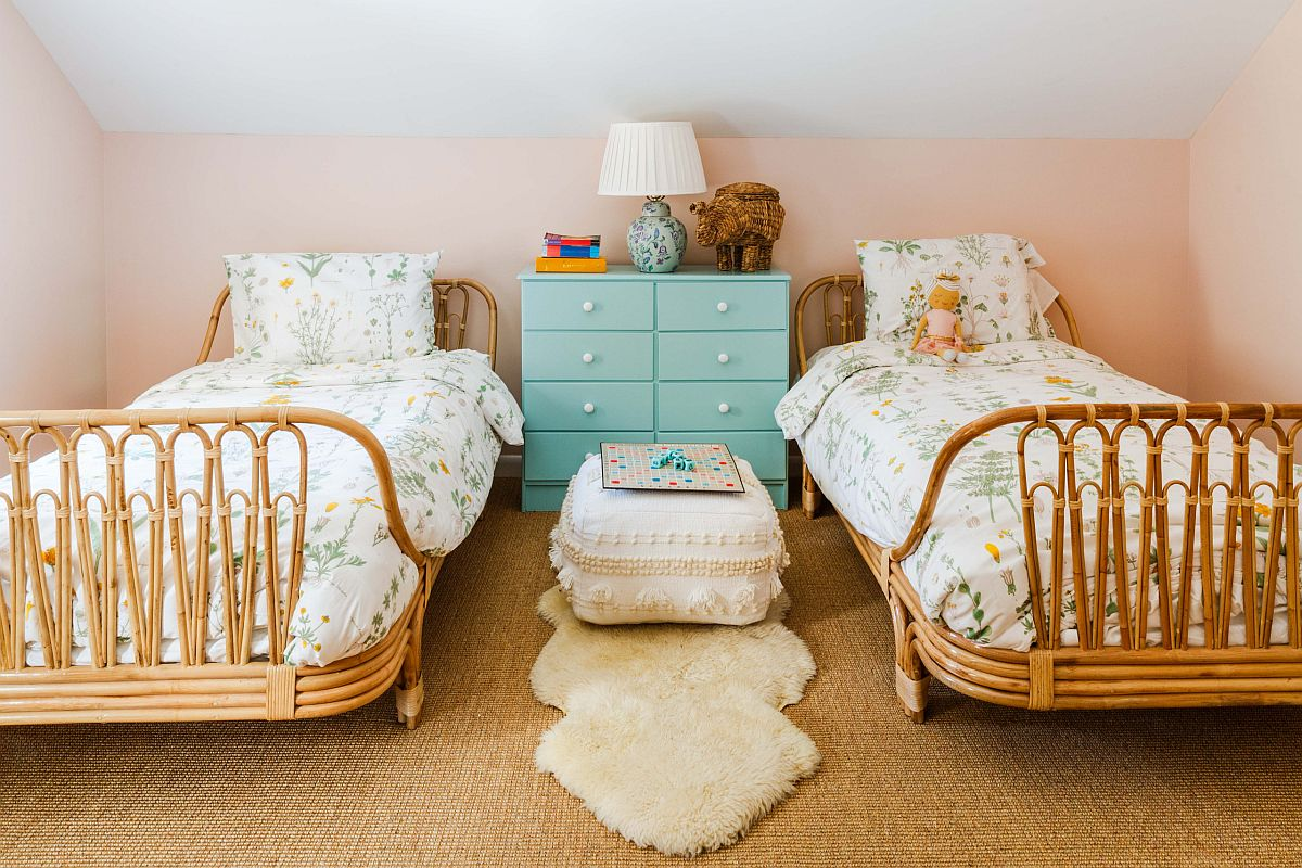 Shared girls' bedroom with twin rattan beds and smart furniture