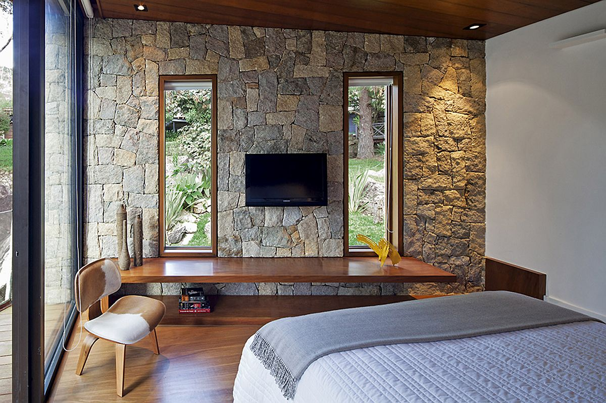 Simple floating wooden desk se against stone walls inside the bedroom