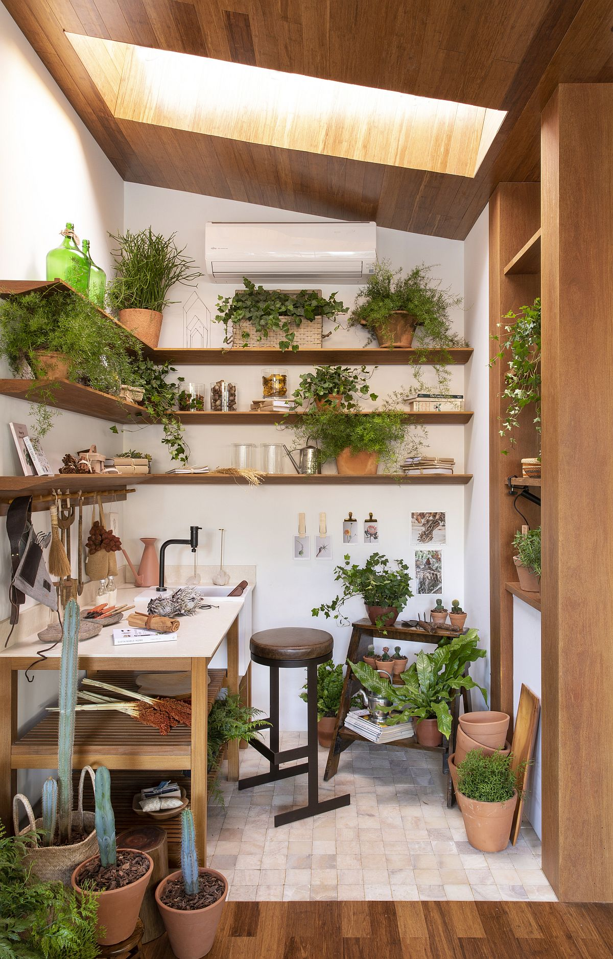 Skylight brings natural light into this small crafting room full of greenery