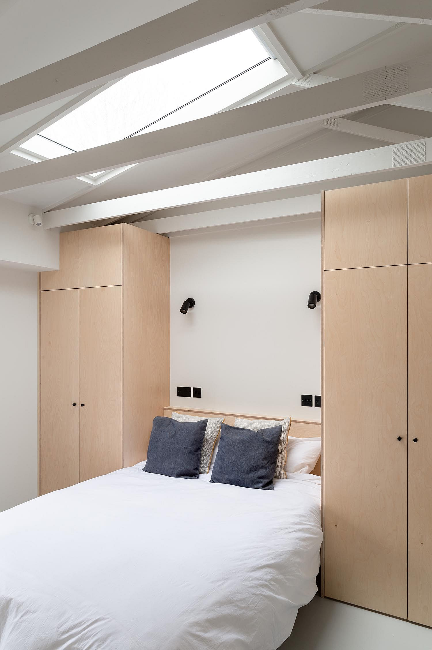Skylight ushers ample naural light into the bedroom in white