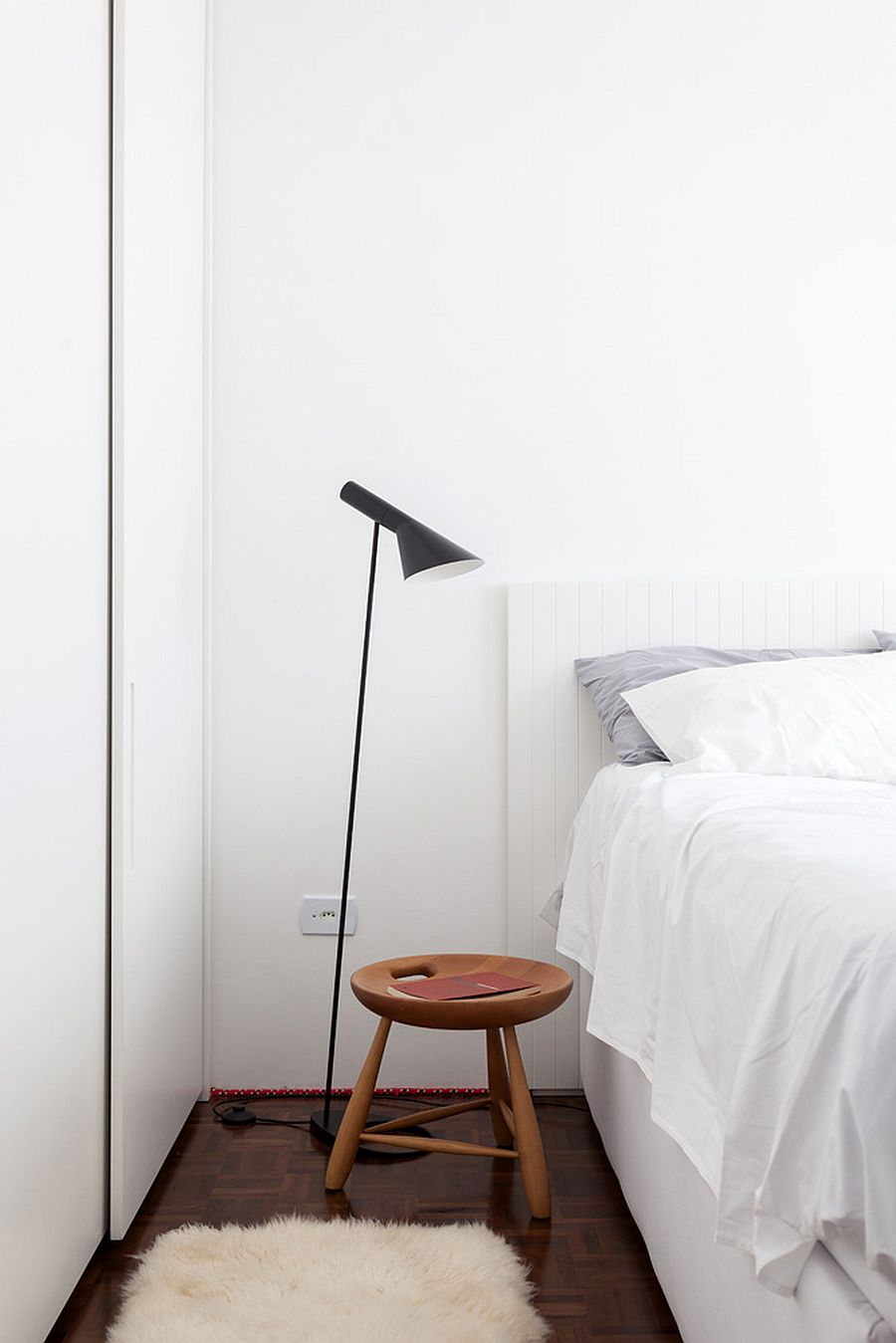 Sleek floor lamp and small bedside table for the tiny bedroom in white
