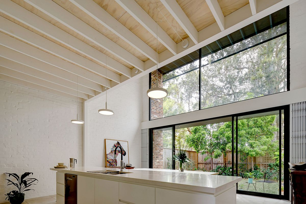 Sliding-glass-doors-and-glass-walls-connect-the-white-modern-kitchen-wih-the-rear-yard-85183