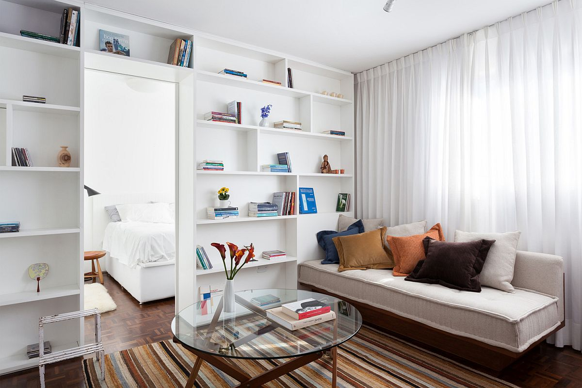 Small modular sofa rests next to the spacious bookshelf in the living area along with striped rug that adds color