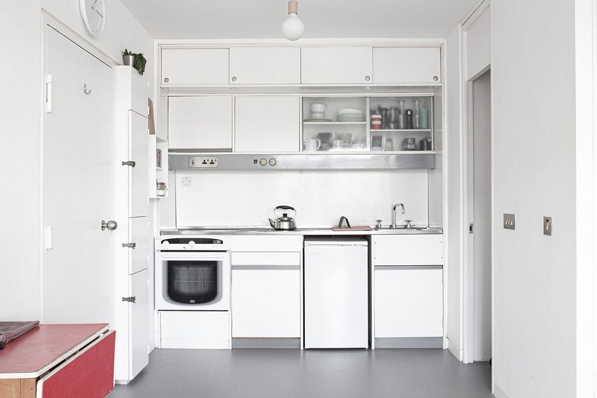 Small single-wall kitchen in white inside the studio apartment in London