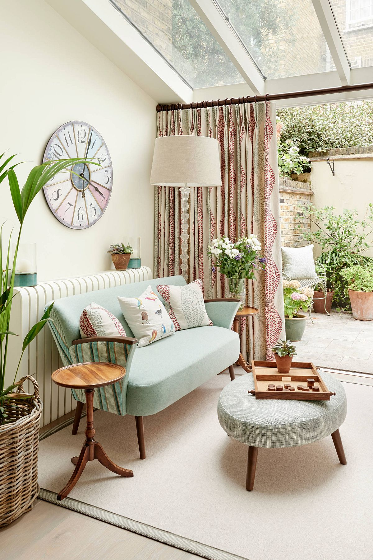 Sunroom in white with decor in pastel hue combines modernity with eclectic charm