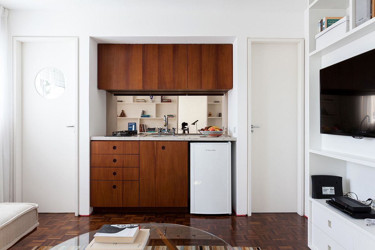 Tiny kitchen with a single-wall design ha wooden shelves and wooden cabinets