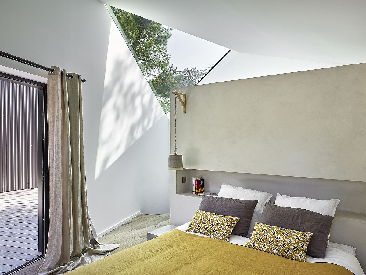 Triangular cutoauts bring natural light into the bedroom on the upper level clad in white