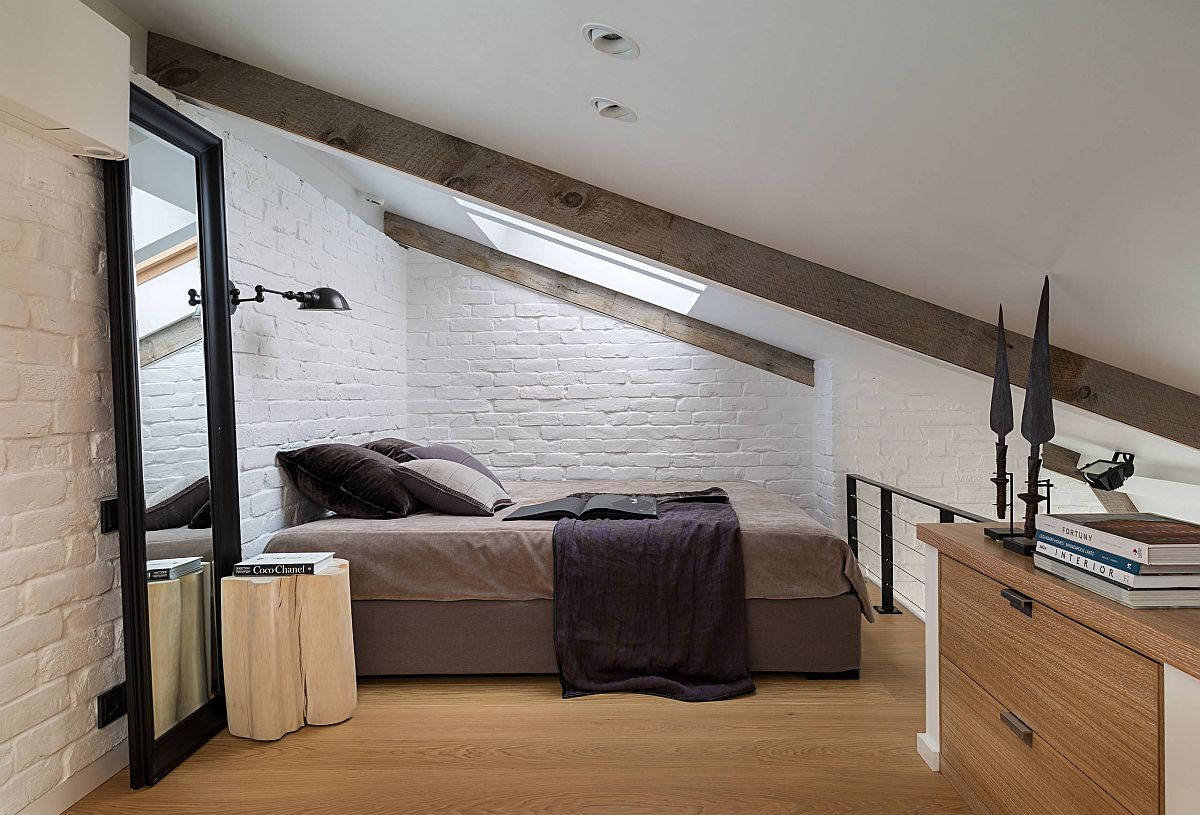 Ultra-small atic bedroom with sloped ceiling and large mirror that gives it a more spacious look