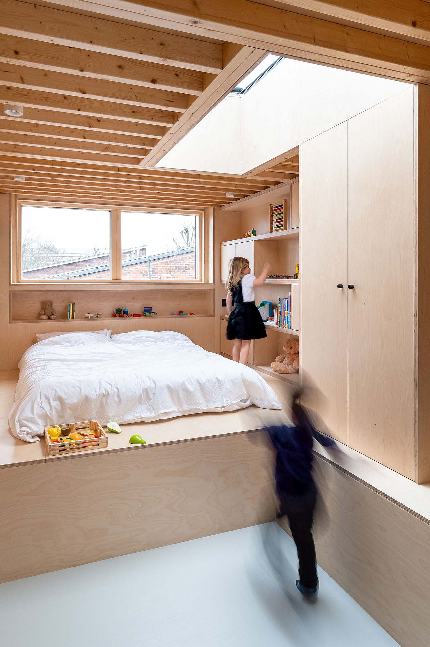 Upper level kids' bedroom with exposed ceiling beams in wood and a backdrop in white