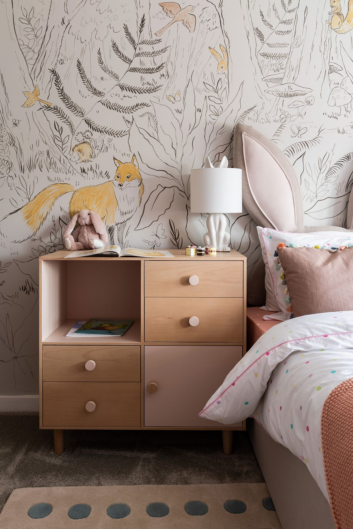 Wallpaper brings the charm of woods into this contemporary girl's bedroom in white and light pink