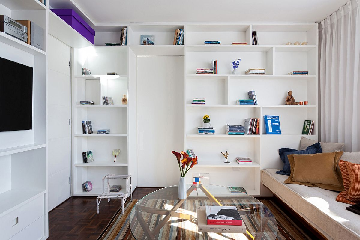 White bookcase inside the tiny Brazilian apartment hides door to the bedroom that is hidden behind