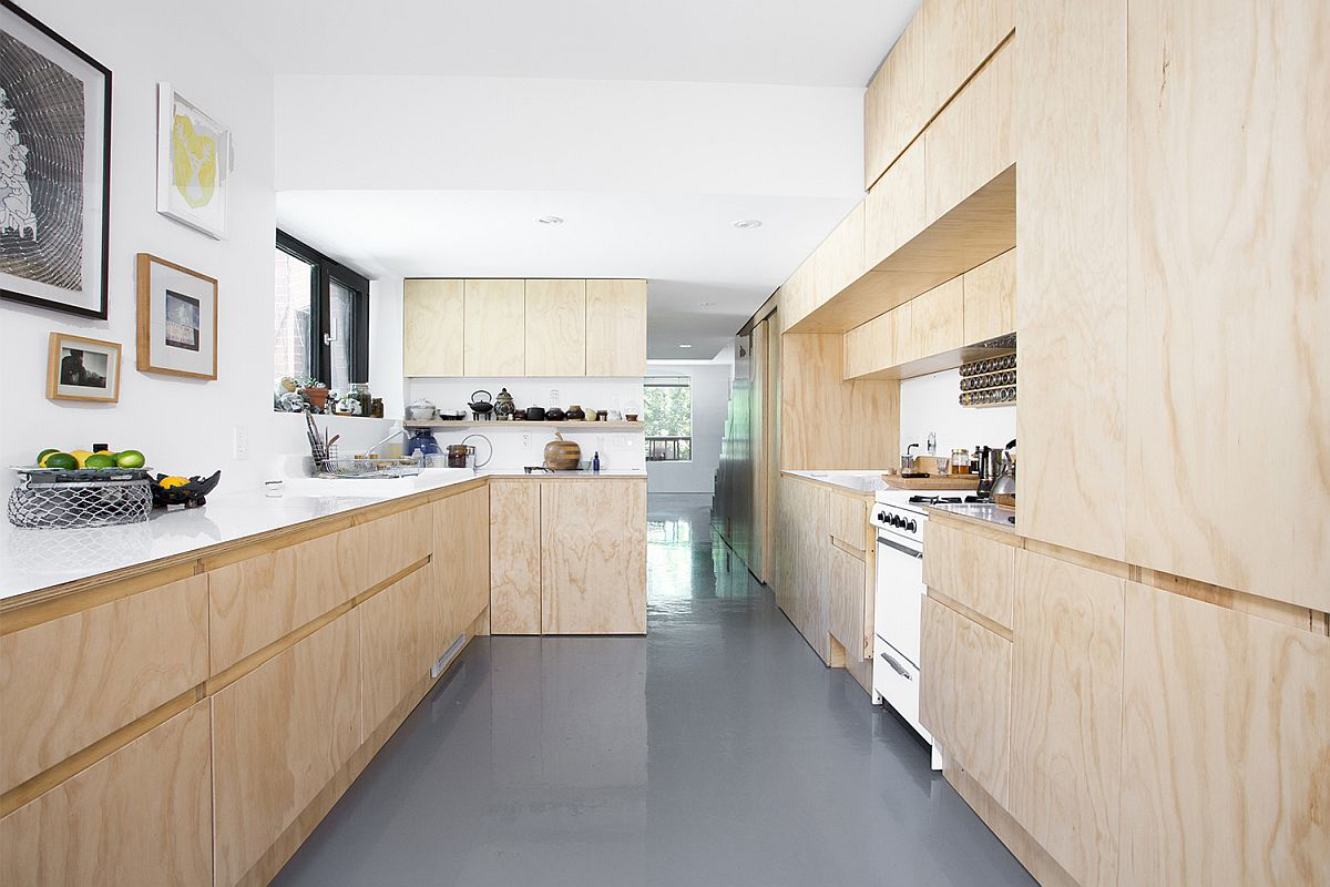 Wood and white kitchen of the revamped apartment unit with polished epoxy floor in gray