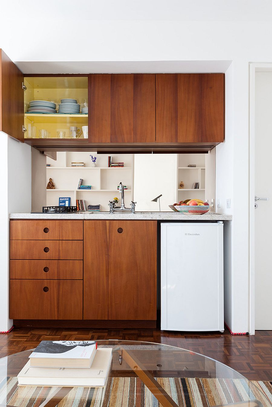 Wooden cabinets bring warmth to the small studio apartment in white